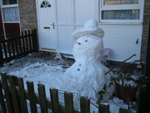 A Snowman in someone's garden.