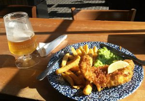 A plate with Fish and Chips and a pint of San Miguel.