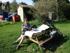 Nikki sitting at a picnick table with a map open