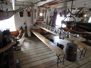 Inside the gun bay of an old warship with tables set for lunch