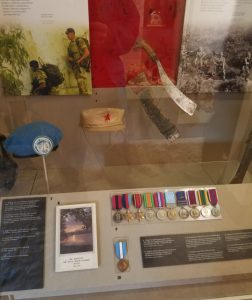A display in the Welsh Fuseliers museum, showing a Parang, some medals and some hats.