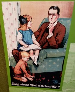"""A man sitting on a chair with 2 children. Looking thoughtfull as they ask him """"Daddy, what did YOU do in the great war"""""""