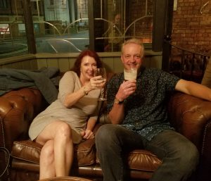 Pam and Dave with drinks, sitting on a leather settee.