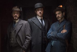 Three characters from Ripper street standing in a dark alley.