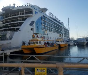 "Enormous floating hotel and small yellow ""dolphin"" boat"
