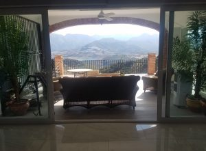View throug living room showing mountains and a reservoir