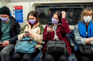 Poeple wearing facemasks on public transport in the UK