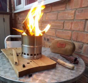 A lit camping stove, that burns sticks.